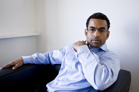 흑인 사업가, 40, 의자에 앉아 사무실 대기실에서 40 스톡 콘텐츠