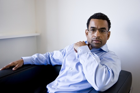 African American businessman, 40, in office waiting room sitting in chair