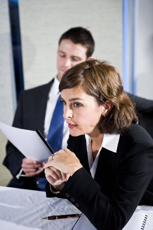 Businesswoman, 40s, watching presentation and with male colleague sitting behind, focus on woman photo