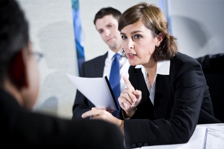 Businesswoman talking in meeting with colleagues reading report