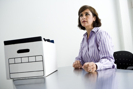 Female office worker, 40s, sitting at office table with cardboard file storage box photo