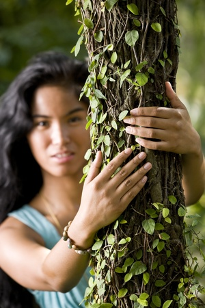 pacific islander: Beautiful woman, 20 years, of Pacific Islander ethnicity.  Focus on tree trunk