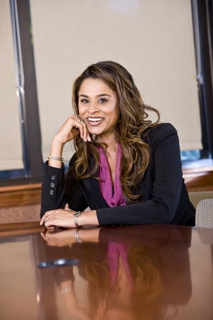 indian ethnicity: Professional worker sitting in boardroom, Indian ethnicity, 30s Stock Photo