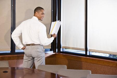 보고서를 읽고, 어깨 너머로보고 아프리카 계 미국인 회사원의 후면보기 스톡 콘텐츠