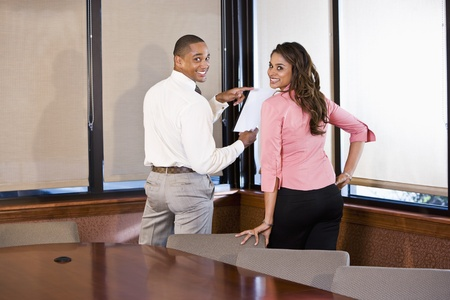 African American businessman and Indian businesswoman meeting in office boardroom 스톡 콘텐츠