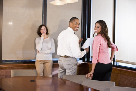 Three multiethnic office workers reading report in boardroom, focus on couple on right photo