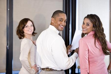 회의실에서 보고서를 읽는 세 multiethnic 회사원, 오른쪽에 커플에 초점 스톡 콘텐츠