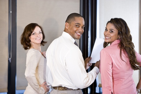 Three multiethnic office workers reading report in boardroom, focus on couple on right Stock Photo - 8555194