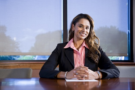 Professional worker sitting in boardroom, Indian ethnicity, 30s Stock Photo