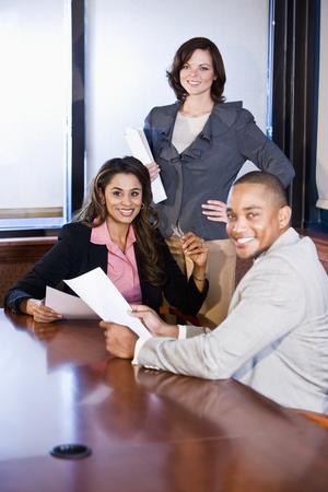 회의실에서 보고서를 읽는 세 다민족적인 사무실 근로자, 중간에 여자에 초점