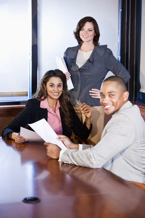 Three multiethnic office workers reading report in boardroom, focus on woman in middle Stock Photo - 8554805
