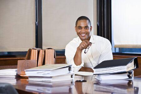 회의실에서 테이블에 문서의 스택과 함께 아프리카 계 미국인 회사원 스톡 콘텐츠