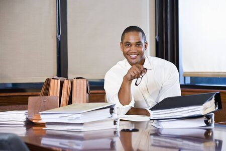 African American office worker with stacks of documents on table in boardroom Stock Photo - 8554799