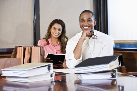 African American businessman and Indian businesswoman meeting in office boardroom with stacks of documents, focus on man