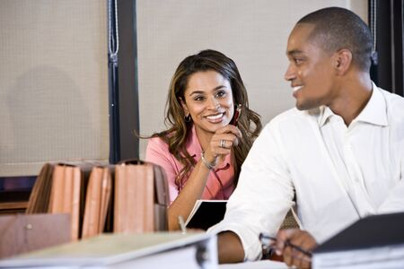 auditors: African American businessman and Indian businesswoman working together in office, focus on woman Stock Photo