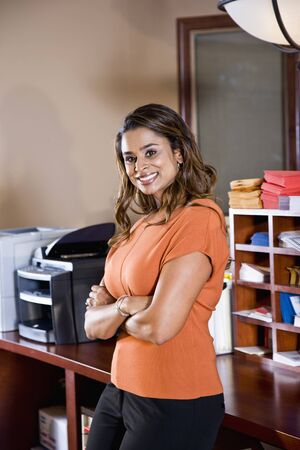 Female office worker, Indian ethnicity, standing in mailroom with office equipment Stock Photo