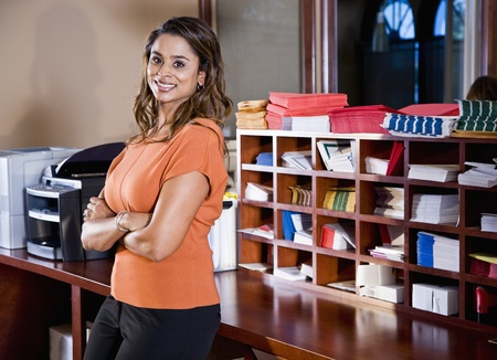 mailroom: Female office worker, Indian ethnicity, standing in mailroom with office equipment Stock Photo