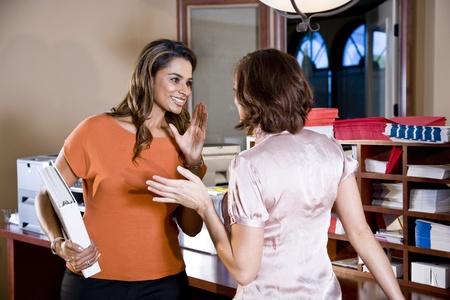 Multiethnic office workers gossiping in mailroom Stock Photo - 8555205