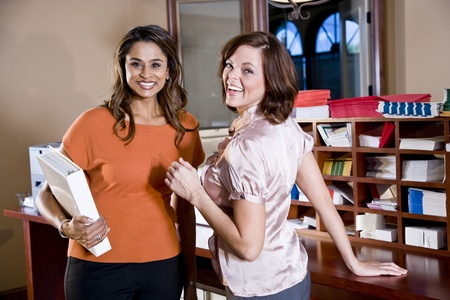 Multiethnic office workers talking in mailroom, main focus on woman in orange shirt