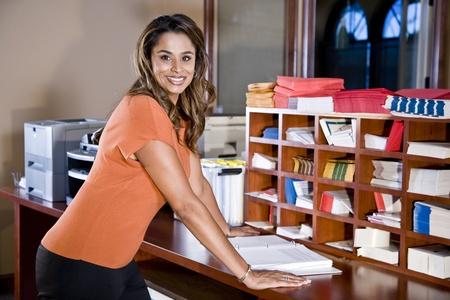 fotocopiadora: Empleado de oficina femenina, indio de origen �tnico, de pie en la sala de correo con equipo de Oficina