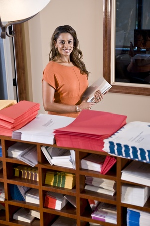 mailroom: Female office worker, Indian ethnicity, holding document binder in mailroom