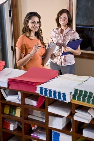 Multiethnic office workers standing in mailroom, focus on woman in orange shirt