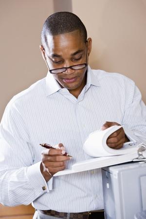アフリカ系アメリカ人オフィス ワーカー ドキュメント バインダーを見直し、プリンターに傾いた