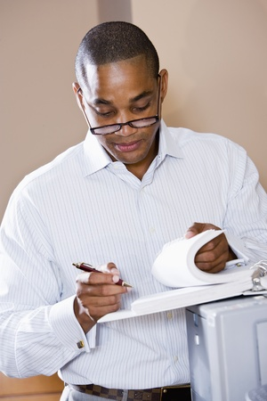 African American office worker reviewing document binder, leaning on printer