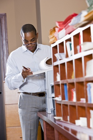 African American office worker reviewing document binder, leaning on printer in mailroom Stock Photo - 8555213