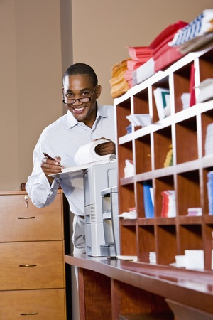 African American office worker reviewing document binder, leaning on printer in mailroom