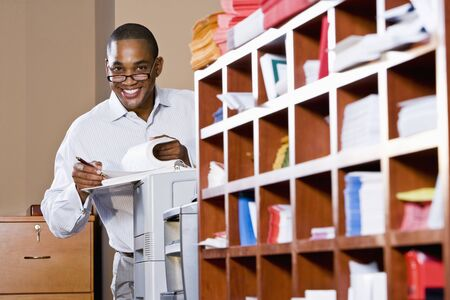 mailroom: African American office worker reviewing document binder, leaning on printer in mailroom