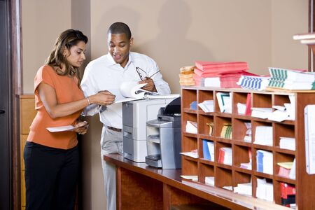 mailroom: African American businessman and Indian businesswoman working together in office