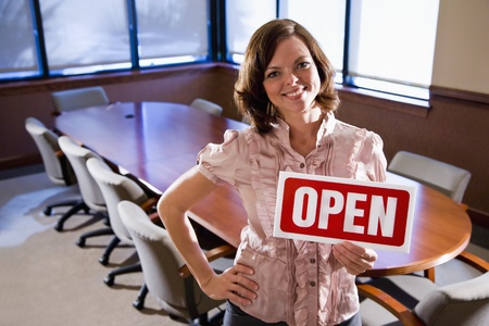 business sign: Young office worker holding open sign in empty boardroom