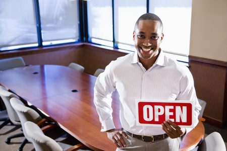 African American office worker holding open sign in empty boardroom photo