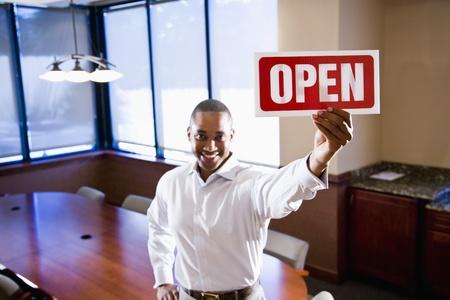 空の会議室、記号に焦点を当てるオープン サインを保持しているアフリカ系アメリカ人の事務員