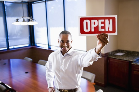 African American office worker holding open sign in empty boardroom, focus on sign photo