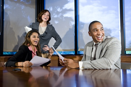 executive assistants: Multiethnic office workers in boardroom watching presentation, laughing, focus on man