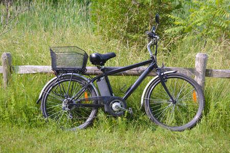 日当たりの良い夏の日の公園の木製の柵に電動自転車。側から撮影します。自然照明、フィルターなし。E モーター、パワー バッテリー、ギアのビ