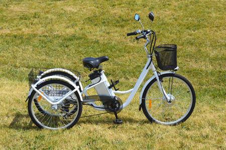 晴れた夏の日の公園で自転車の電動三輪車や。側から撮影します。自然照明、フィルターなし。3輪バイクの e モーターと電源バッテリーの表示。 写真素材