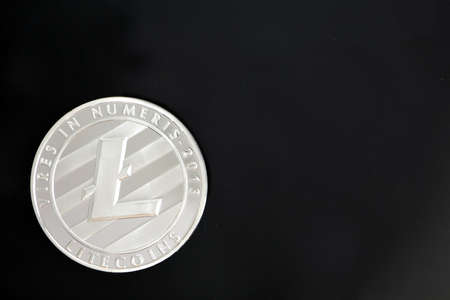 Litecoin, LTC, a cryptocurrency coin isolated on black background with copy space for text. Crypto currency smart contract technology concept photo.