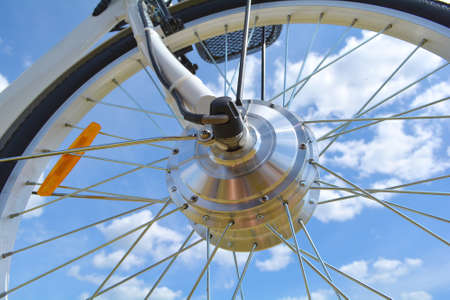 Wheel of the electric bicycle view from below. E bike motor with light reflections. Unfiltered, with natural lighting and blue sky and clouds.