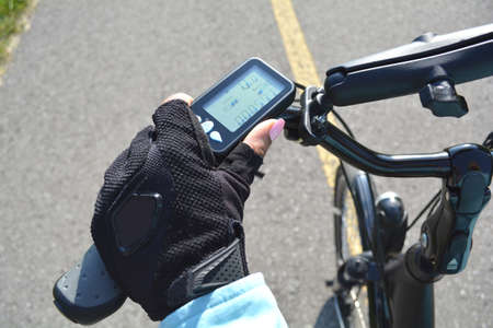 Woman hand with bright pink nails on the electric bicycle handle with computer. Healthy life style concept. Hand holding e bike handlebar with ebike scooter display.