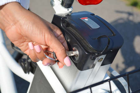 Women cyclist hold the key of the electric bicycle battery pack. Female switch powered e bike with the key in the park in sunny summer day.  Close up shot.