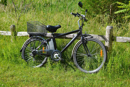 Electric bicycle on the wood fence in the park on sunny summer day. Shot from the side. Unfiltered, with natural lighting. The view of the e motor, power battery and gear.