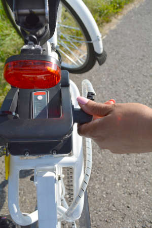 Close up of battery pack of electric bicycle. Women with pink nails manicure connect the battery with motor on her e bike. Stock Photo