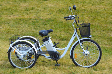 Electric trike or bicycle in the park in sunny summer day. Shot from the side. Unfiltered, with natural lighting. The view of the e motor and power battery of the three wheel bike. Stockfoto