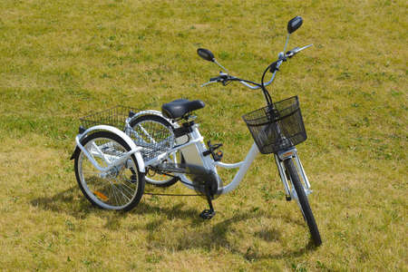 Electric trike or bicycle in the park in sunny summer day. Shot from the side. Unfiltered, with natural lighting. The view of the e motor and power battery of the three wheel bike. Stock Photo