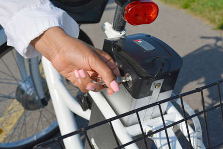 Women with pink nails and manicure hold the key of the electric bicycle battery pack. Female switch on the powered e bike with the key in the park in sunny summer day. The view of the e bike motor.