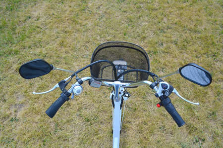 Electric bicycle rudder or helm in the park on sunny summer day. Shot from above. The view of e bike steering wheel with bell, brakes, speed switch, and  power battery control device and mirrors.