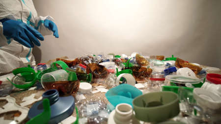 Volunteer cleaning and sorting pile of plastic. Collecting and separating one time use plastic trash. Pollution and environmental problem with homes and household waste management. Save the planet. Stockfoto